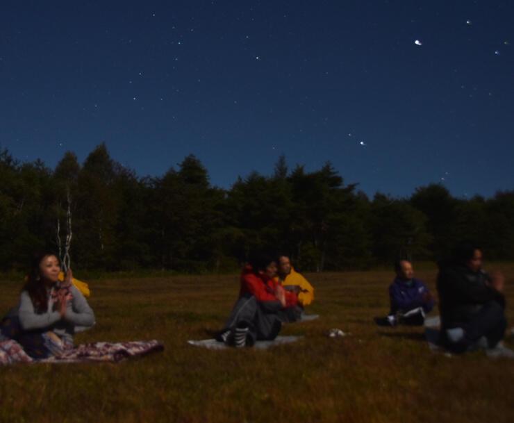 高原の空気を吸いながら、星空の下でヨガをする協議会の会員ら