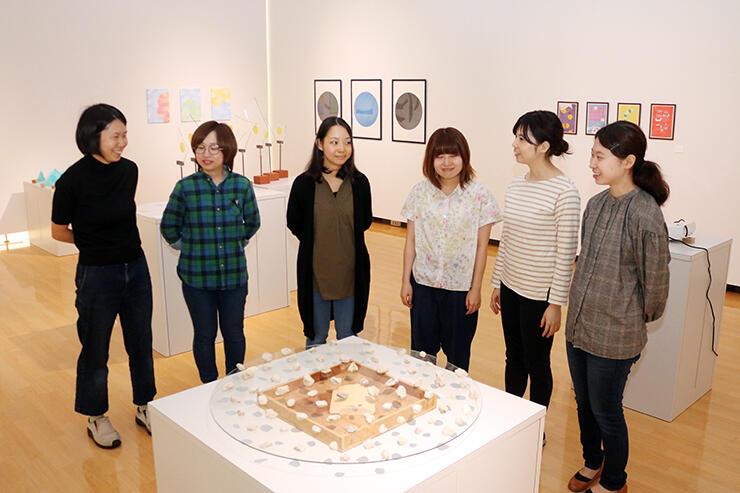 多彩な作品が並んだ会場で語り合うメンバー