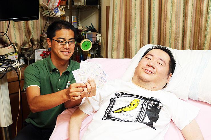 イベントのチラシを持ち笑顔を見せる友人(左)と板橋さん