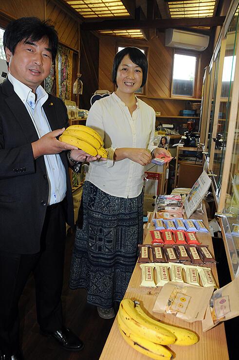 フェアトレードに配慮した商品が並ぶ店内で、竹内さん(右)から大会で販売する商品の説明を受ける山田委員長