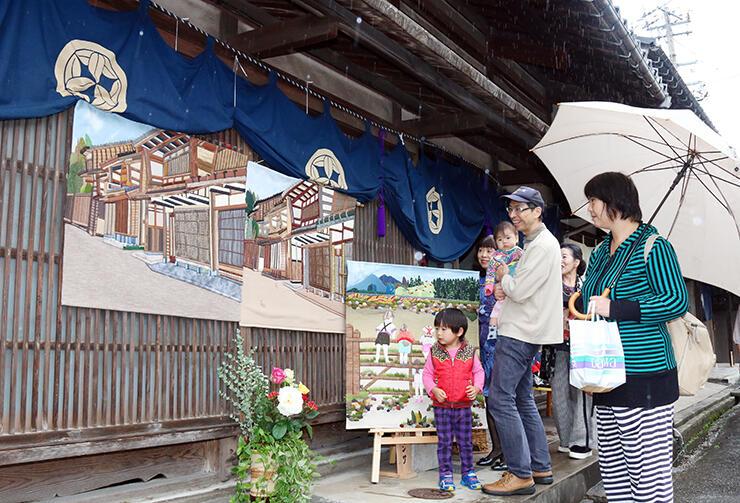 千本格子の家屋前に展示された作品を楽しむ人たち