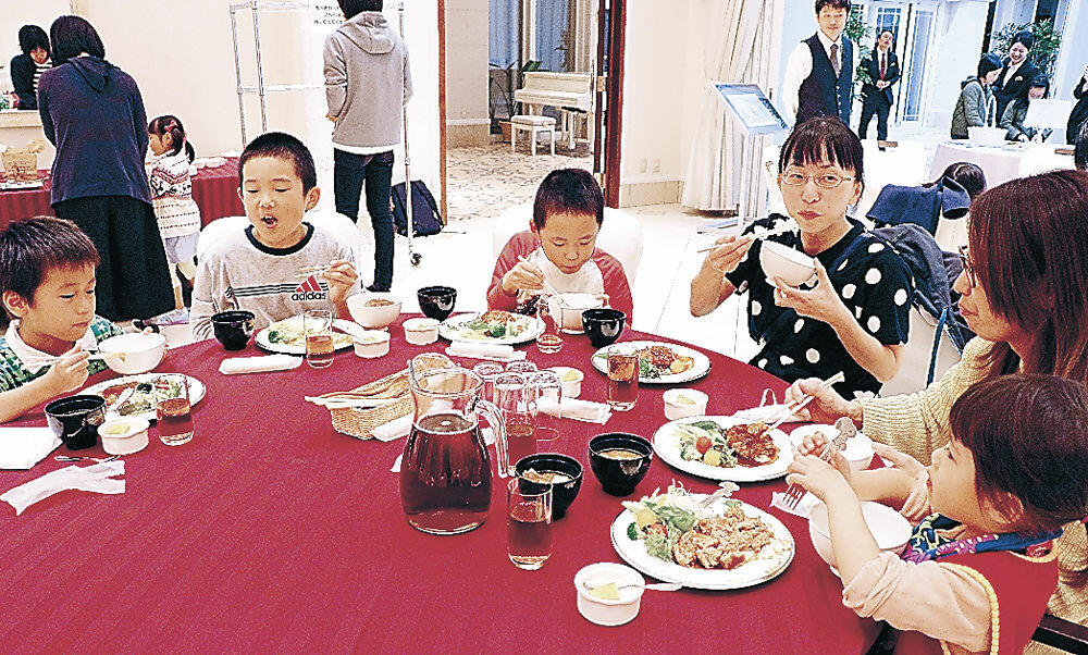 子ども食堂が開設された結婚式場で、料理を味わう子どもたち=藤江北4丁目