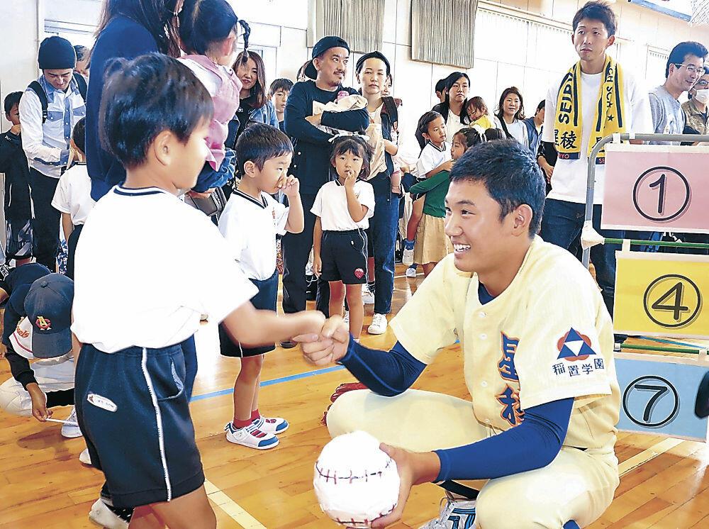 園児と笑顔で握手する奥川投手=白山市千代野小体育館