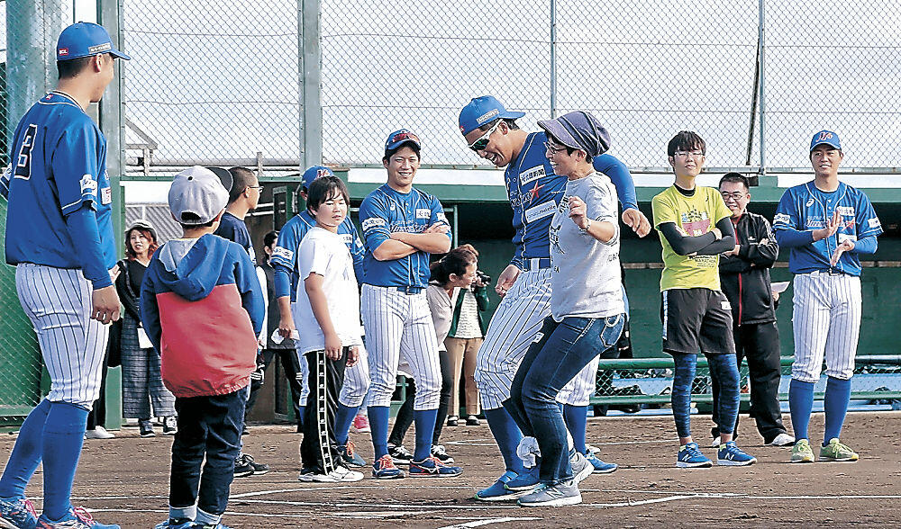 二人三脚リレーで仲良く走るファンと選手=金沢市安原スポーツ広場