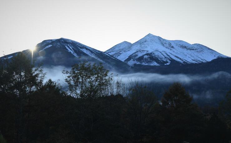 日没間際、雪をかぶった姿を見せた乗鞍岳=22日午後4時、松本市安曇