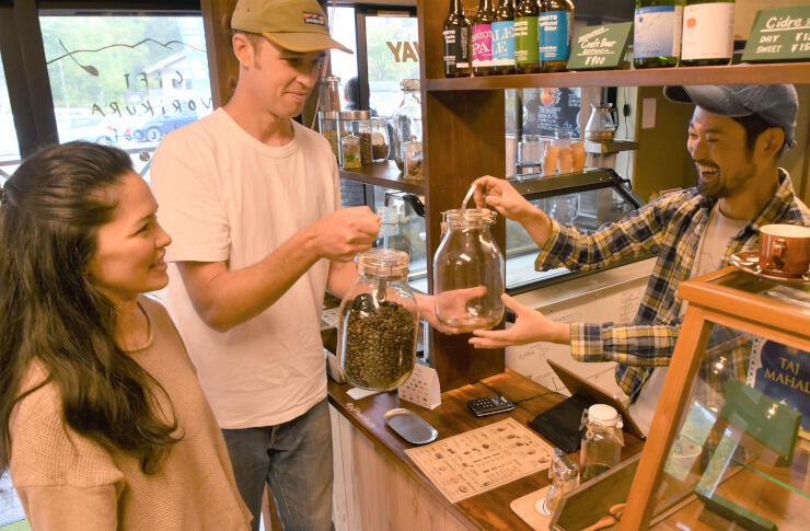 コーヒー豆の入った瓶をカフェまで届け、空の瓶と交換するセツさん(中央)とハナさん(左)