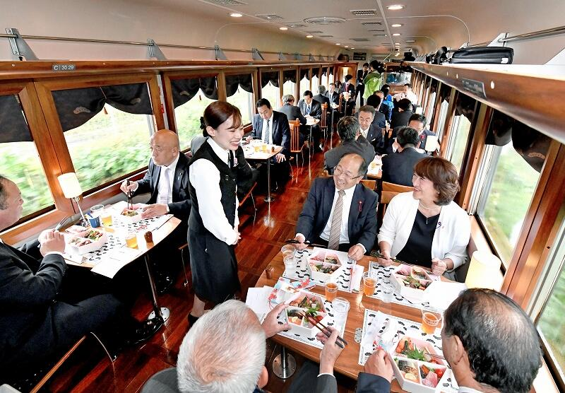 JR小浜線に初めて乗り入れた観光列車「丹後くろまつ号」で食事を楽しむ関係者=10月25日、福井県敦賀市内