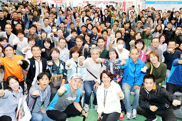 大会ゲストの有森さん(前列右から2人目)や金さん(同3人目)と一緒に拳を上げて意気込む参加ランナーたち=富山市総合体育館