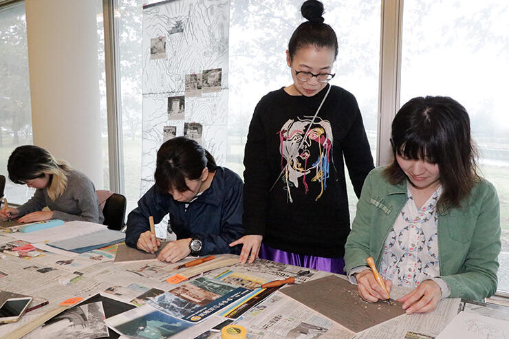 風間さん(右から2人目)の指導を受けながら木版画を制作する参加者