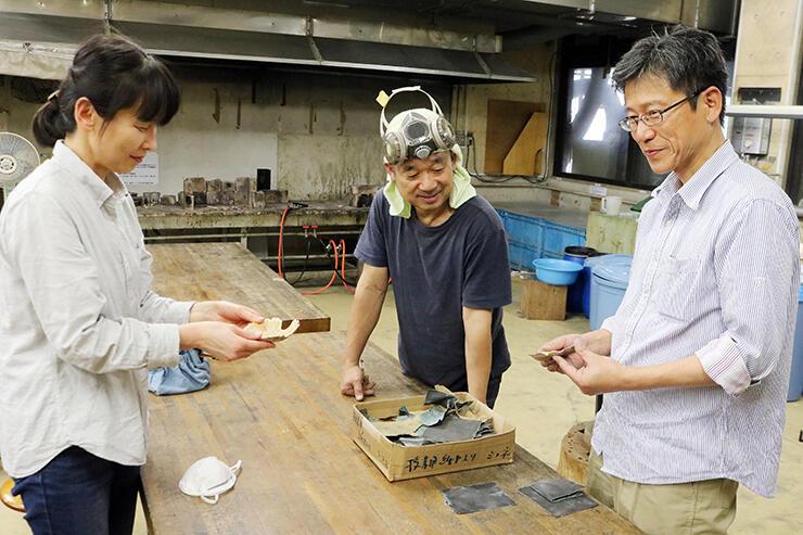 鋳型から取り出した皿を手に取る参加者と三船教授(中央)
