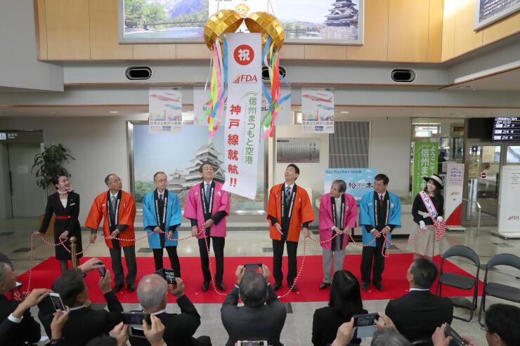 くす玉を割り、神戸線就航を祝った記念セレモニー=松本市の県営松本空港