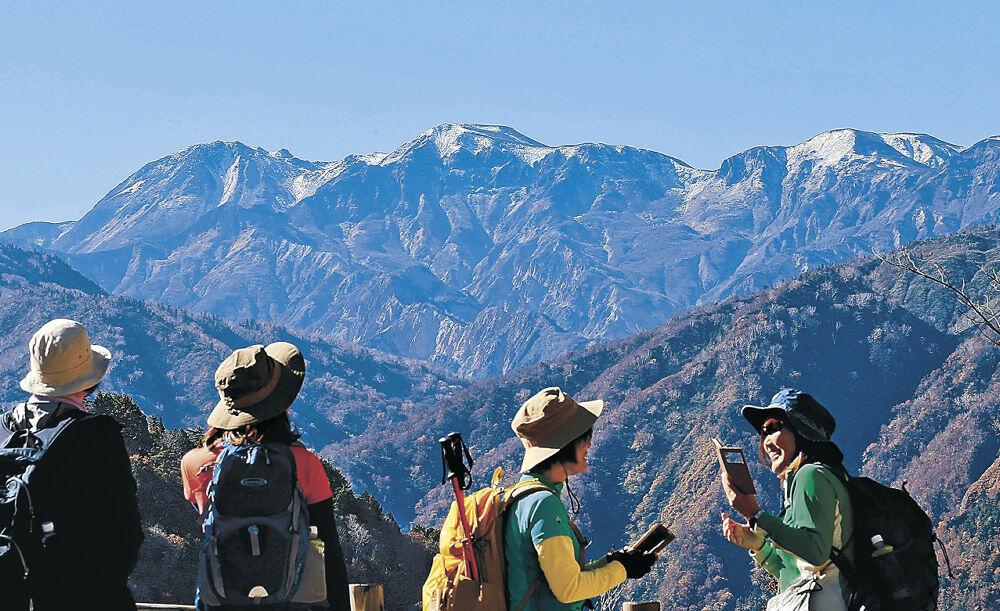 冠雪した山並みを望む登山客=28日午前10時、白山市の白山白川郷ホワイトロード「とがの木台駐車場」
