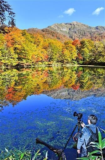 赤や黄に色づいた木々が水面に映り込む刈込池=10月28日、福井県大野市上打波