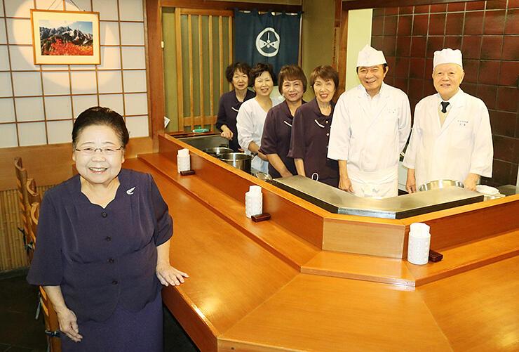 店のカウンター席に立ち、お客さんへの感謝の思いを伝える五十嵐勝枝さん(左)やスタッフ=県庁前天米