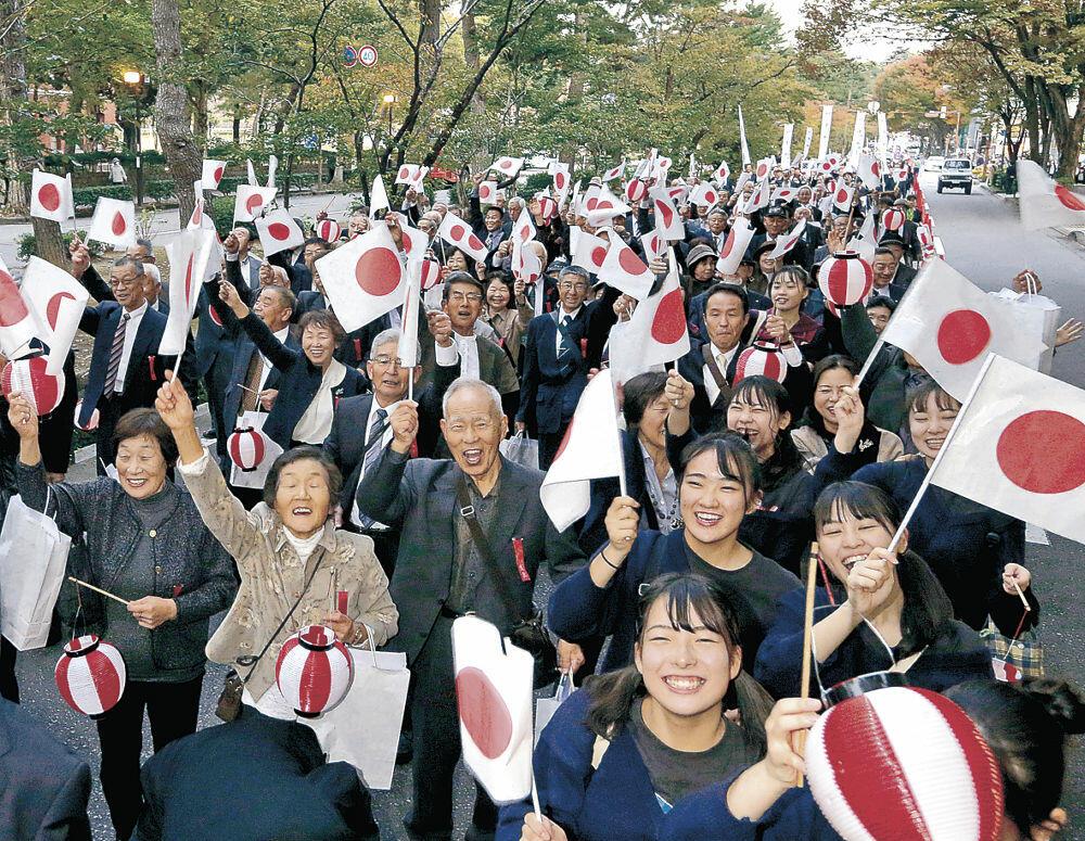 中心街を行進する奉祝パレード参加者=金沢市広坂1丁目