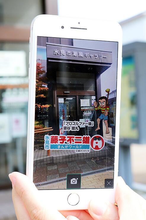 スマートフォンに取り込んだ「プロゴルファー猿」のキャラクター画像。街角の映像と重ねられる