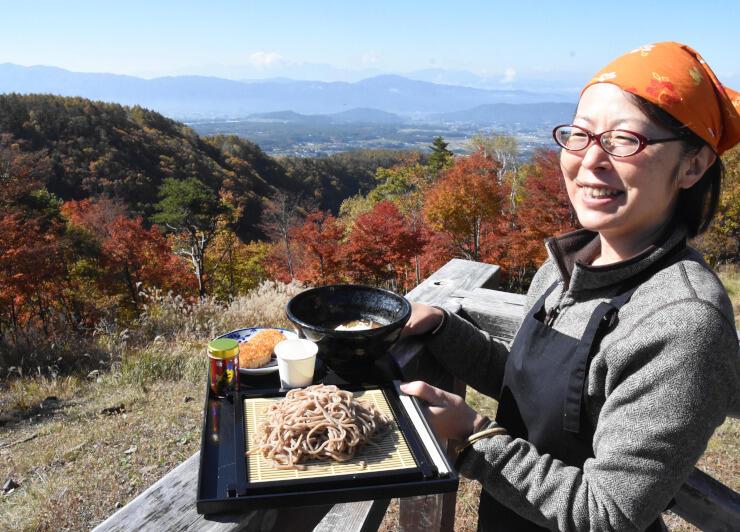 店舗から50歩ほどの距離にある展望台に立つ晶栄さん。紅葉、茅野市街地、山々を眺めながらそばを味わえる