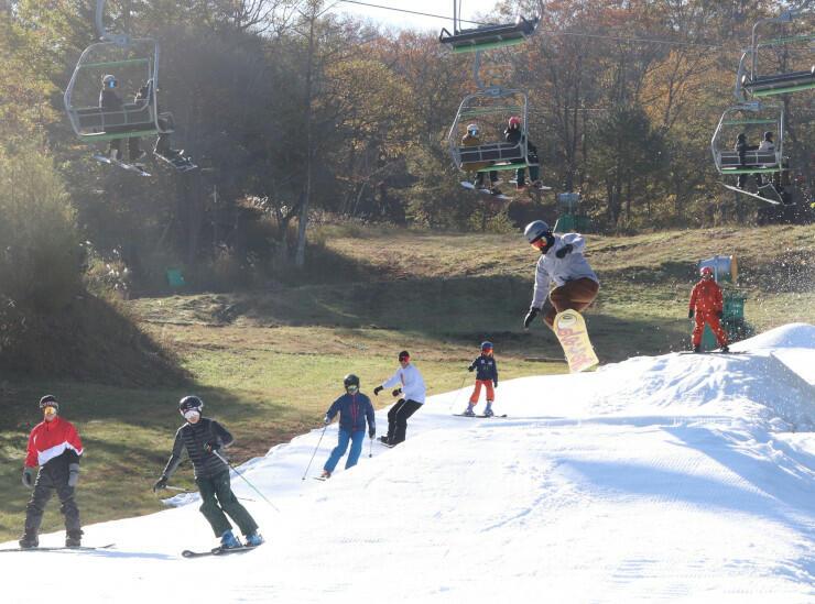 紅葉に囲まれたゲレンデでスキーやスノーボードを楽しむ人たち=2日
