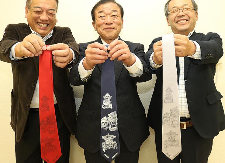 完成したネクタイを紹介する沼田会長(中央)ら