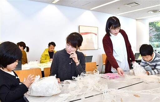 コウゾを素材にした創作に挑戦する参加者。右から2人目は作家の加茂さん=11月4日、福井県あわら市金津創作の森美術館