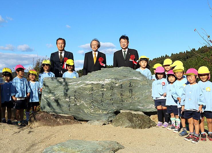 石碑を前に、子どもたちと一緒に記念撮影する中西さん(中央)ら