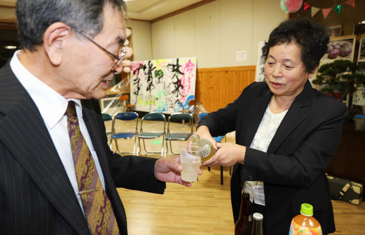 赤根大根の焼酎と麦焼酎を混ぜた「清内路」を注ぐ桜井さん(右)