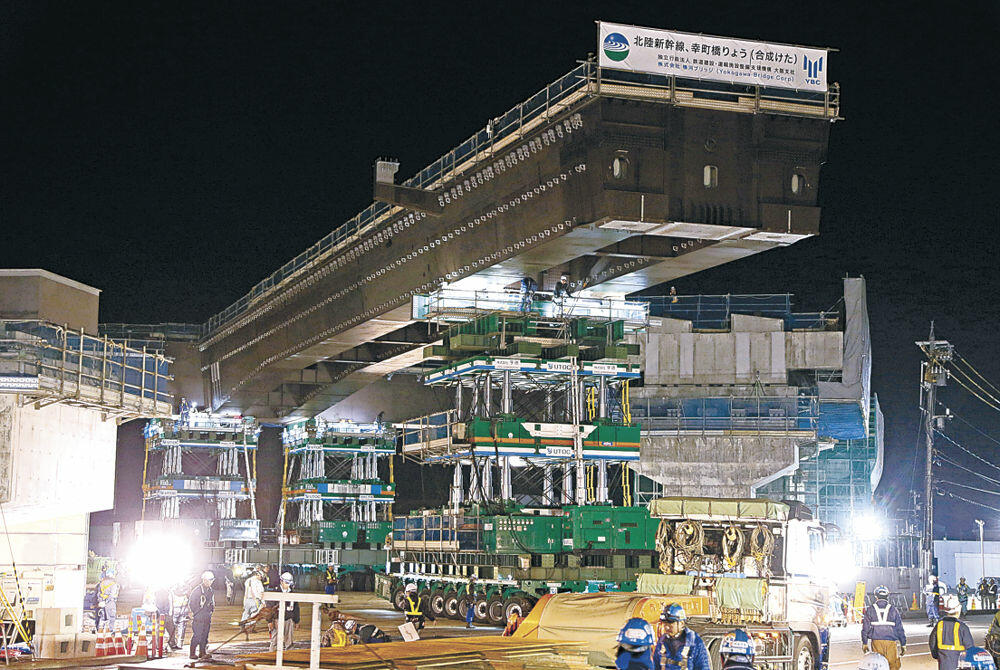 架設作業が始まった国内最大級の橋げた=9日午後10時、小松市幸町3丁目