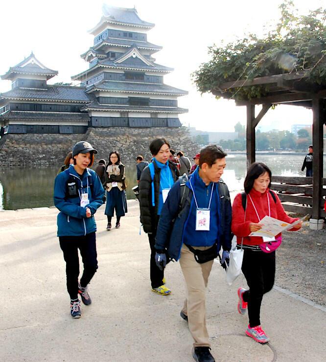 「集印帳」を首から下げ、地図を片手に松本城公園を歩く参加者たち