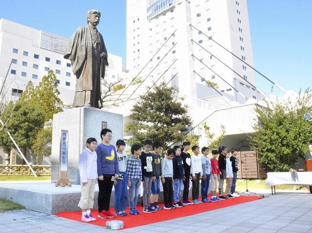 岡倉天心の像の前で児童が誓いの言葉を述べた顕彰祭=11月8日、福井県福井市中央公園