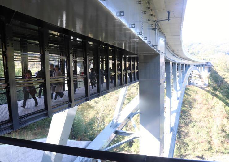 天龍峡大橋の下部に併設された歩道「そらさんぽ天龍峡」を歩きながら、天竜川流域の景色を楽しむ人たち