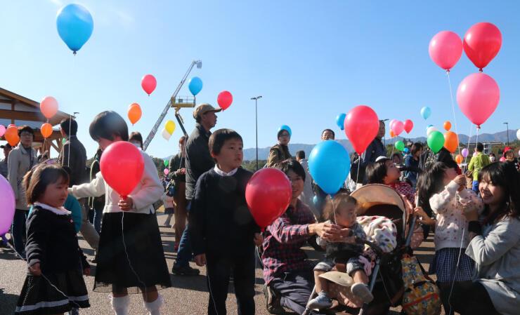 記念イベント会場の一つ「天龍峡パーキングエリア」では、訪れた親子連れらが一斉に風船を飛ばし、道路開通を祝った