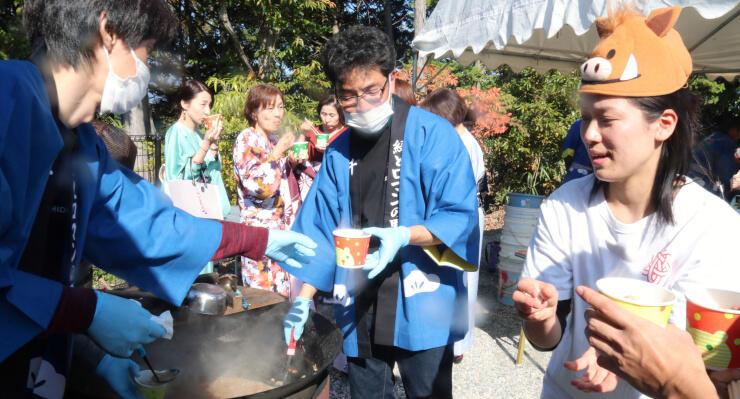 天竜川左岸地域の農産物などを使ったイノシシの鍋を味わう人たち