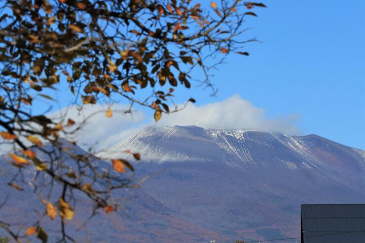 紅葉と共演する今季初冠雪の浅間山=12日午前11時、佐久市猿久保の駒場公園から
