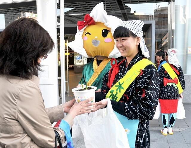 水仙を配布する児童ら=11月15日、福井県福井市のJR福井駅西口
