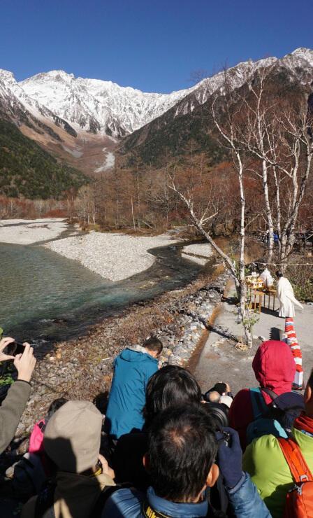 雪化粧した山並みに向かって梓川のほとりで行われた上高地の閉山式