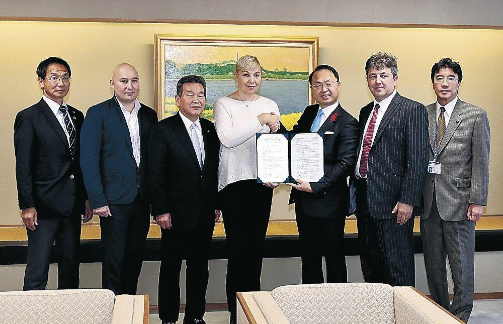 協定書を交わし親交を誓う連盟と市の出席者=金沢市役所