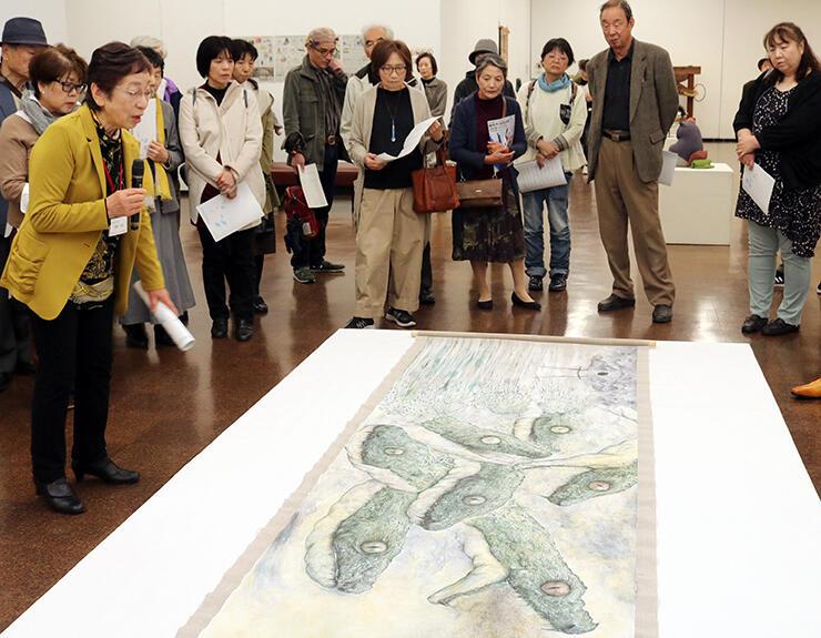 優秀賞受賞作「絵巻-EMAKI-」の前で、浦野さん(手前左)の解説に耳を傾ける来場者=県民会館