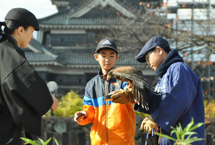 松本城二の丸御殿跡で鷹狩りを体験する小学生(中央)