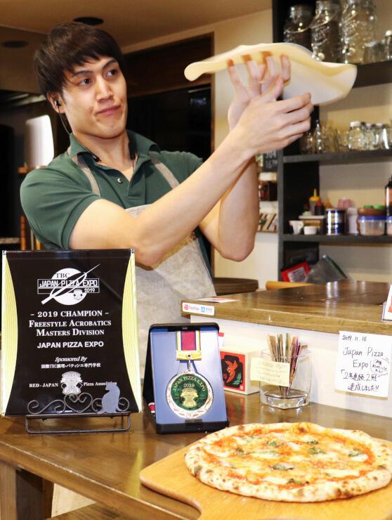 ピザ回しの練習で使うピザ生地の形をしたゴムを回す赤羽さん