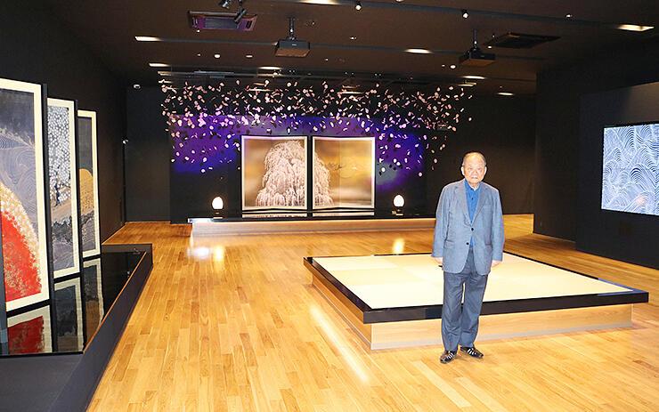 加山又造の作品が並ぶ展示室を案内する伊勢会長=イセ食品富山事務所