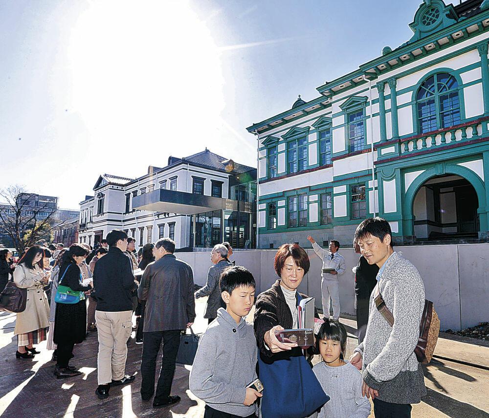 真新しい国立工芸館前で記念撮影を楽しむ親子連れ=金沢市出羽町