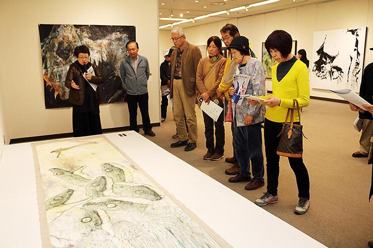 渡邊副館長(左)の講評を聞きながら作品を鑑賞する来場者