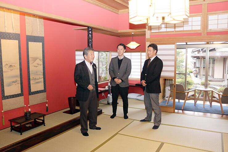 石動・柏屋の一室に立つ柏山さん(左)と塩谷商事の社員