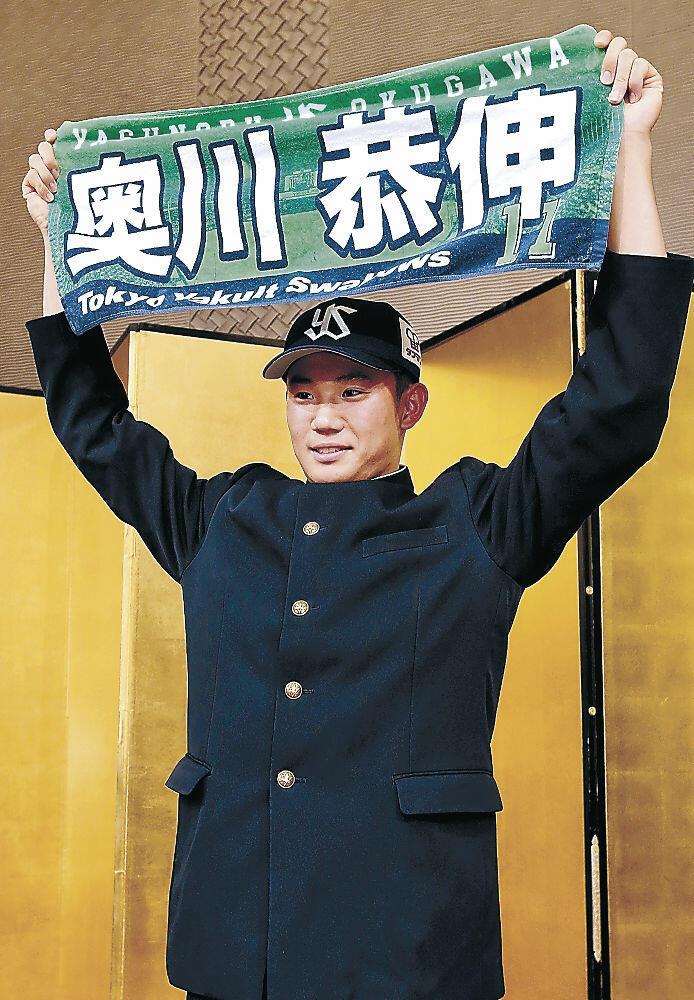 ヤクルト入団が決まり、名前と背番号入りのタオルを掲げる奥川=金沢市内のホテル