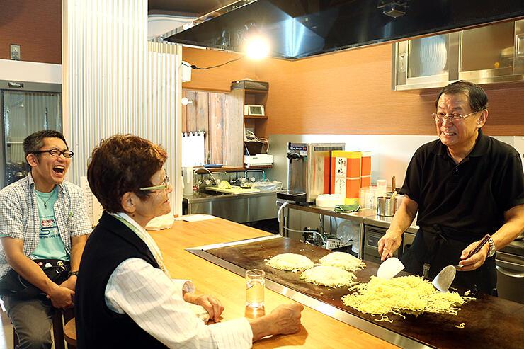 今年10月にお好み焼き店を開業した明石さん(右)=射水市放生津町