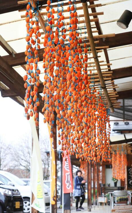 旬彩館の店頭を彩る「柿すだれ」=27日、高森町