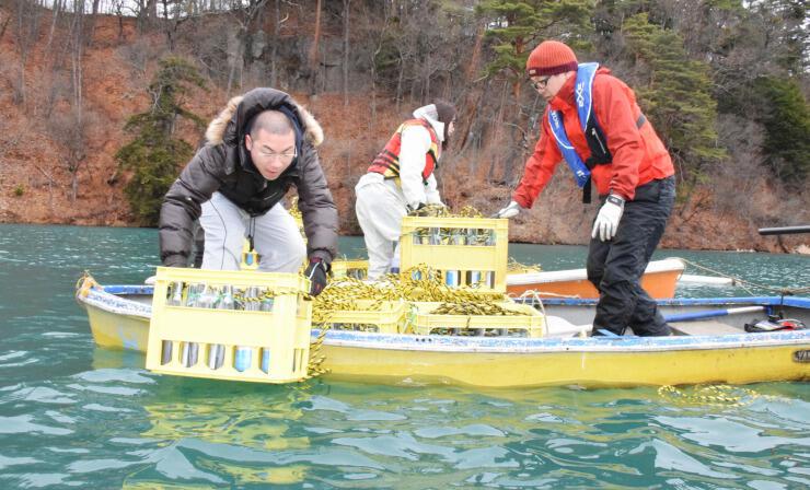 ケースに入った日本酒を湖に沈める鷹野さん(右)ら