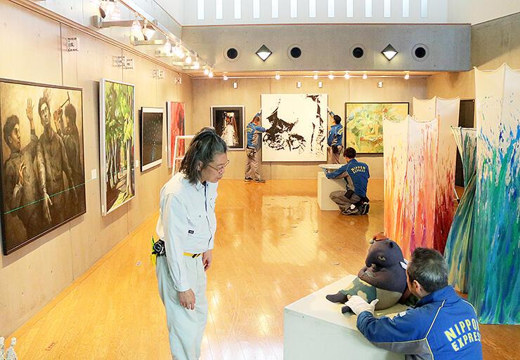 鈴木さん(左)の指導で展示作業を進めるスタッフ