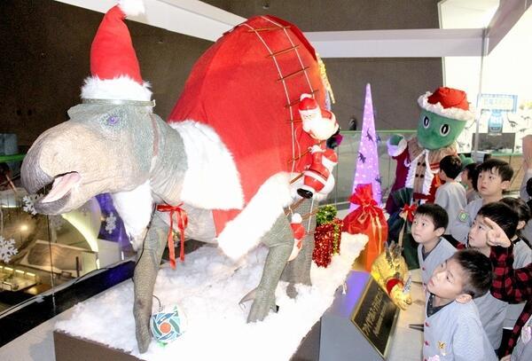 サンタクロースの衣装をまとい、楕円球をパスするフクイサウルスの実物大模型=11月29日、福井県勝山市の福井県立恐竜博物館