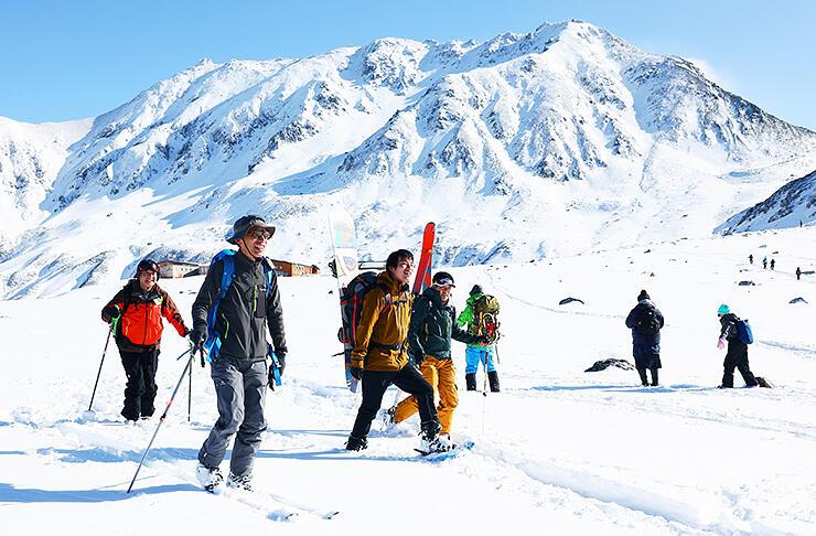 白銀の立山連峰をバックにスキーやスノーシューで散策する人たち=立山・室堂